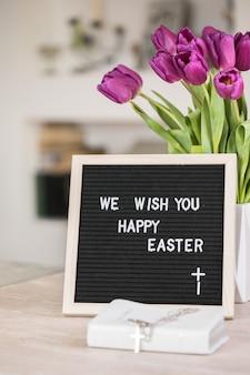 우리는 당신에게 행복한 부활절을 기원합니다 단어와 함께 보라색 튤립 꽃과 편지 보드의 꽃다발