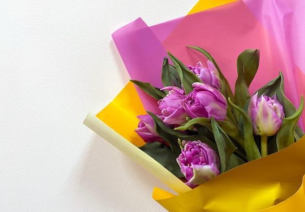 Букет фиолетовых тюльпанов в разноцветной бумаге на светлом фоне