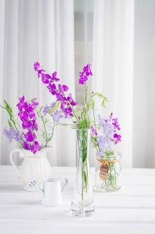 Букет фиолетовых полевых цветов в стеклянной вазе изолированные