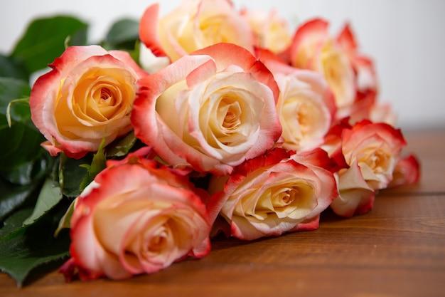 茶色の木製の背景に赤とベージュのバラの花束