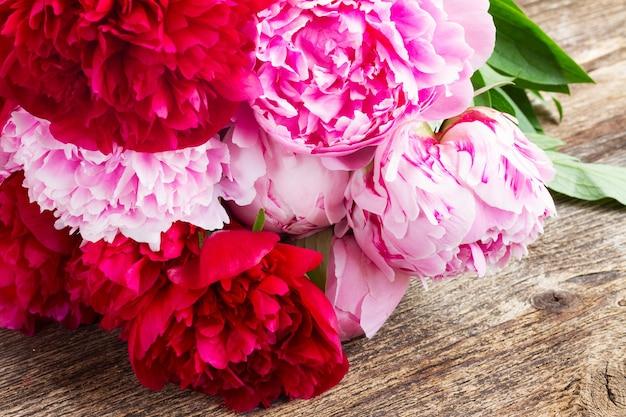 Букет красных и розовых пионов на деревянном столе