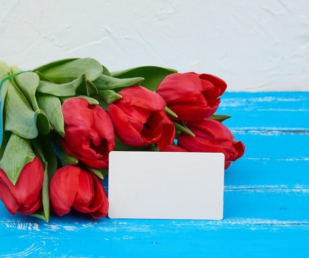 緑の茎と葉を持つ赤い咲くチューリップの花束、花は青い木製のテーブルにあります。