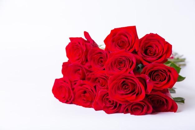 白い表面に赤い(バーガンディ)バラの花束。テキストの場所。閉じる。