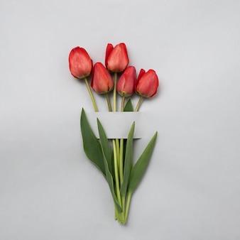 축제 행사나 기념일에 초대하기 위해 회색 배경에 빨간색 또는 분홍색 튤립 꽃다발. 봄과 봄 방학에 대한 최소한의 창의적인 개념. 발렌타인 데이와 어머니의 날.