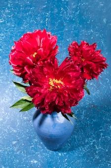 Букет красных пионов в керамической голубой вазе на синем текстурированном фоне. яркая праздничная открытка. цветы для матери или женщины в ее праздничный день. вертикальная ориентация. выборочный фокус.