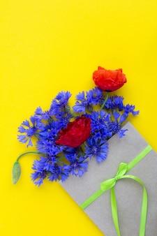 노란 표면에 녹색 리본으로 묶인 봉투에 빨간 양 귀 비와 파란 cornflowers의 꽃다발. 상위 뷰. 공간 복사. 봄 또는 여름 꽃 개념입니다.