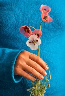 파란 스웨터에 여자의 손에 빨간 양 귀 비의 꽃다발.