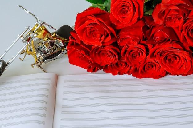 Букет из красных роз и мотоцикл на листе для нот. поздравления музыканту. скопируйте пространство.