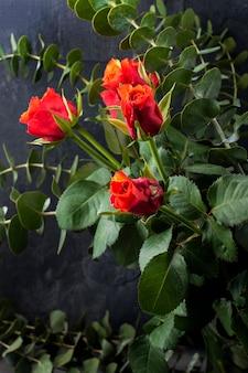 검은 배경에 꽃병에 빨간 장미와 녹색의 많은 꽃다발 나뭇잎