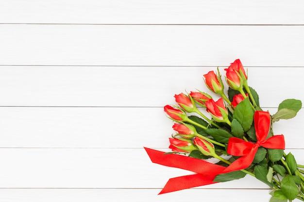 Букет из красных роз, украшенный красной лентой на белом деревянном фоне. вид сверху, копировать пространство