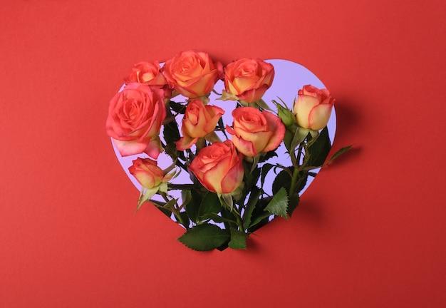 Букет красных роз в бумажной рамке в форме сердца на красной поверхности