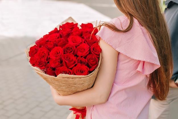 Букет красных роз в руках женщины
