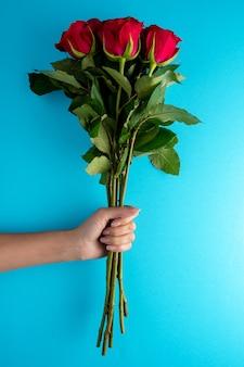 파란색 표면에 여자의 손에 빨간 장미 꽃다발.