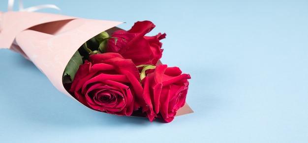 파란색 표면에 빨간 장미 꽃다발