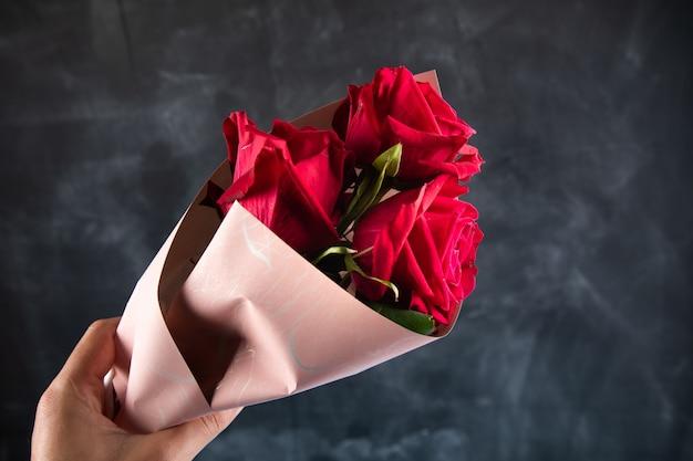 暗い表面に赤いバラの花束