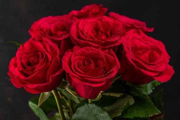 暗い背景に赤いバラの花束。