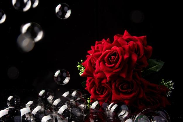 빨간 장미, 검은 배경, 선택적 초점에 비누 거품의 꽃다발.