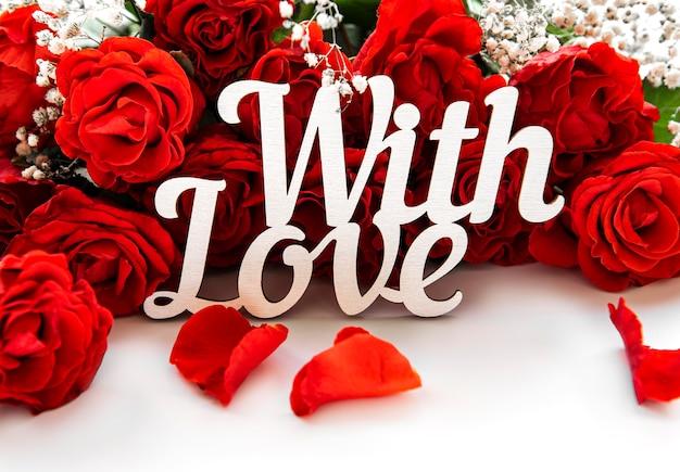 빨간 장미 꽃다발입니다. 발렌타인 데이 개념. 흰색 테이블에 소원과 비문.