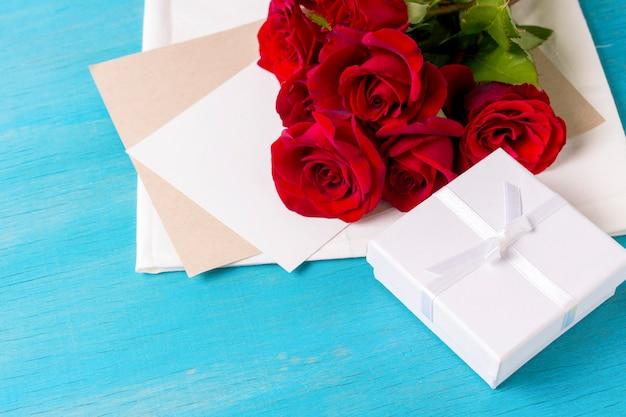 Букет из красных роз белый подарок коробка чистый лист, синий деревянный фон. копировать пространство романтический подарок на день святого валентина
