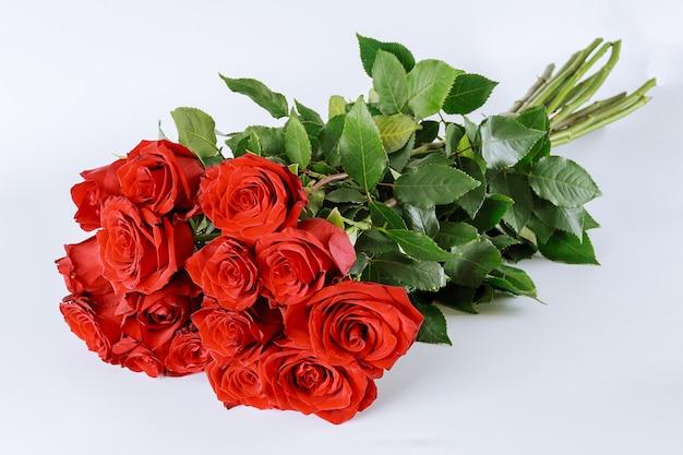 흰색 배경에 무성한 녹색 잎이 있는 빨간 장미 꽃다발
