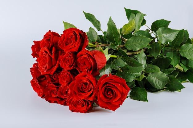 Букет из красных роз с пышными зелеными листьями