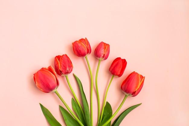 ピンクの背景に赤い春のチューリップの花束。春の花。イースター、バレンタイン、3月8日、お誕生日おめでとう、休日のコンセプト。コピースペース