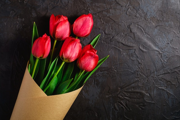織り目加工の黒の背景、上面コピースペースに赤いチューリップの花の花束