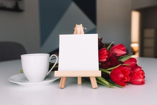 Букет из красных тюльпанов и кофейная чашка. пустая белая рамка. концепция поздравительной открытки