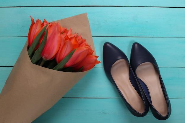 Букет из красных тюльпанов и туфель на высоких каблуках на синем деревянном фоне. праздник день матери или 8 марта, день рождения. вид сверху