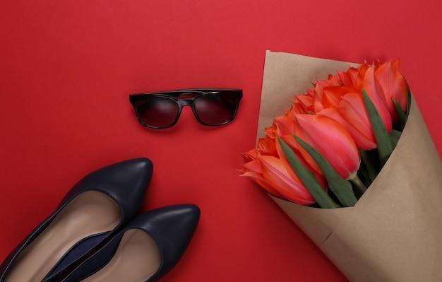 Букет из красных тюльпанов и туфли на каблуках, солнцезащитные очки на красном фоне. праздник день матери или 8 марта, день рождения. вид сверху