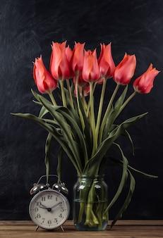 チョークボードの背景に赤いチューリップとレトロな目覚まし時計の花束。学校の静物