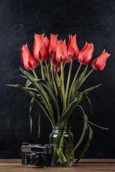 チョークボードの背景に赤いチューリップとレトロなフィルムカメラの花束。学校の静物