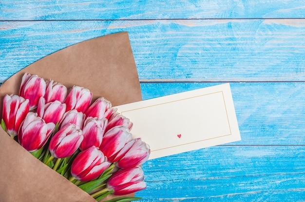 木の板の背景に休日の女性の日とバレンタインデーのための赤いチューリップの花束。