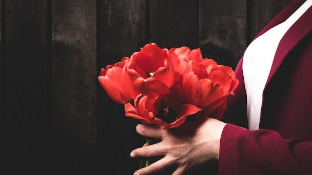 Букет красных тюльпанов в женских руках
