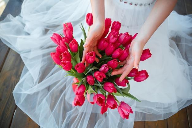 Букет красных тюльпанов в руках девушки