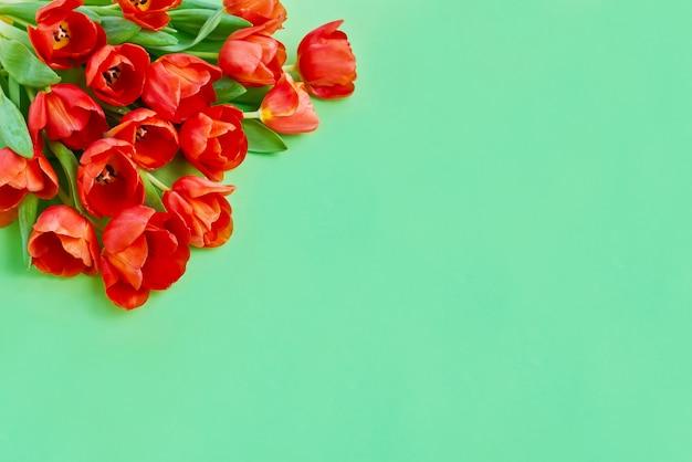 緑の背景に赤いチューリップの花束。