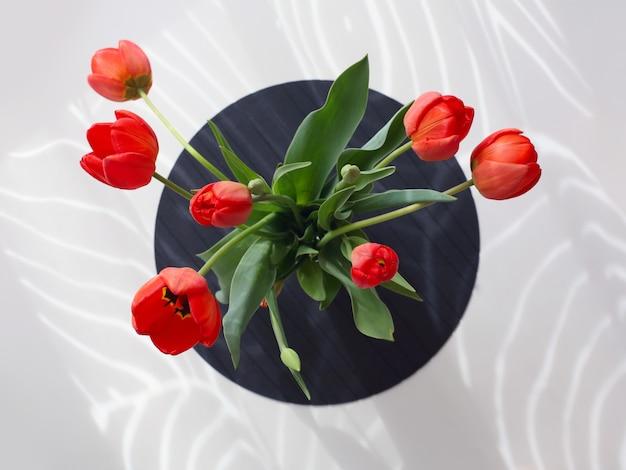 白いテーブルに赤いチューリップの花束。上から見る。