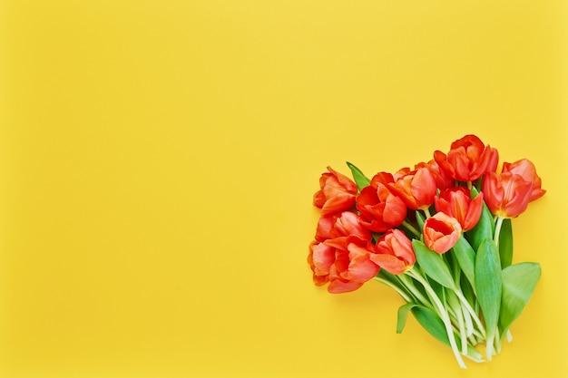 노란색에 빨간 튤립 꽃다발입니다. 아름다운 인사말 카드. 휴일 개념. 텍스트, 상위 뷰 공간을 복사합니다.
