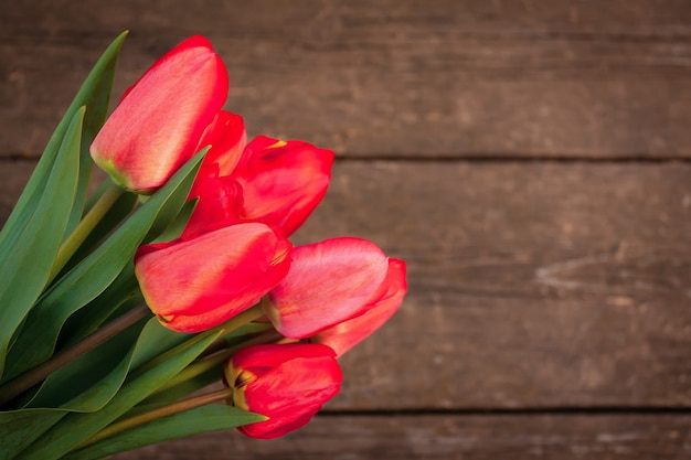 Букет красных тюльпанов на старом деревенском деревянном столе с копией пространства