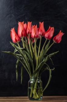 チョークボードの背景に赤いチューリップの花束。学校の静物