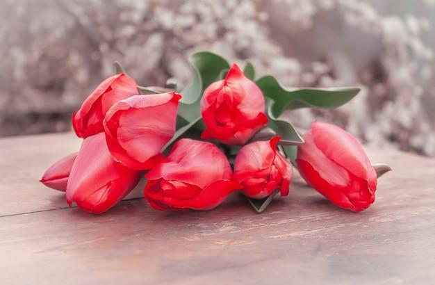 Букет красных тюльпанов на столе в весеннем саду