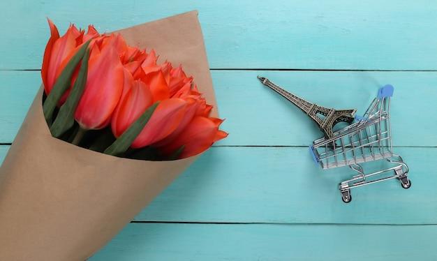Букет из красных тюльпанов, тележка для покупок с фигуркой эйфелевой башни на синем деревянном фоне. вид сверху
