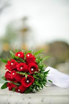 春の日の白い大理石の上の赤い結婚式の花の花束