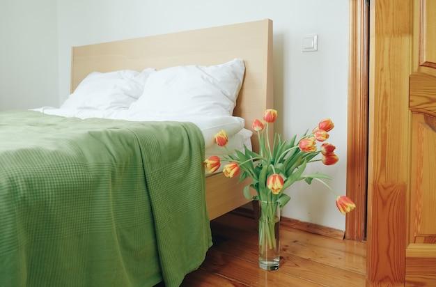 ベッドの背景にある寝室の赤黄色のチューリップの花束。愛の概念