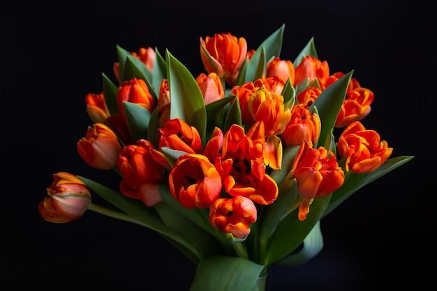 黒の背景に赤黄色のチューリップの花束。閉じる。