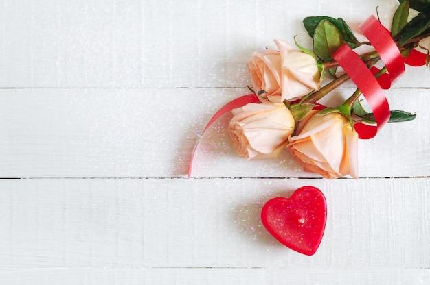 장미와 흰색 나무 배경에 촛불 심장의 꽃다발. 발렌타인 데이의 개념