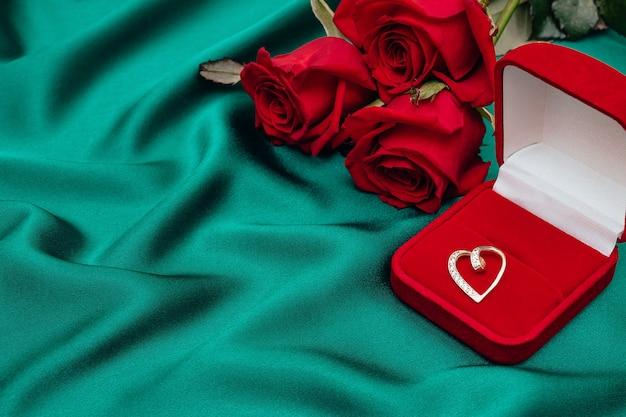 Букет из роз и бархатная подарочная коробка с бриллиантовым кулоном в форме сердца. концепция дня святого валентина