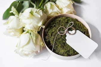 Bouquet of roses and bowl of moss and wedding rings with blank tag