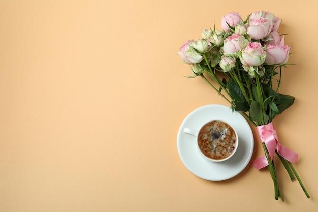 ベージュの背景にバラの花束とコーヒーのカップ