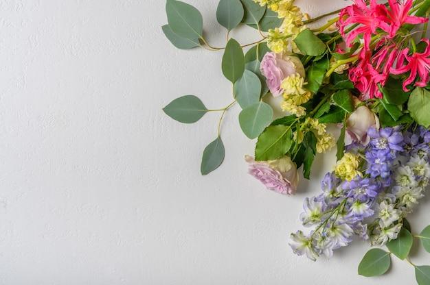 白い背景にバラや他の花の花束。上面図。コピースペース
